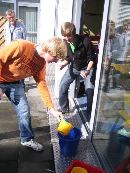 Fabian Umland und Christian Jolst mit Lehrer Burkhard Bender (im Hintergrund) beim Wasserschöpfen.